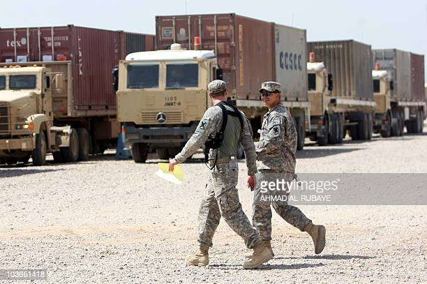 Soldiers walk past army trucks during a logistical operation to clear equipment and heavy machinery from the Balad military base, north of Baghdad,...