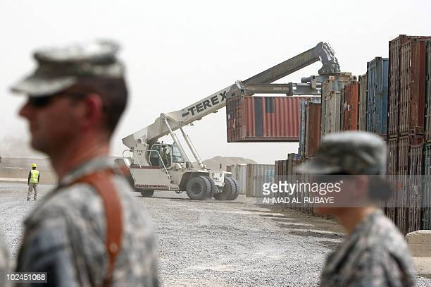 US soldiers walk past containers being transported at Camp Victory a giant sprawling military base on the edge of Baghdad airport on June 24 2010 as...