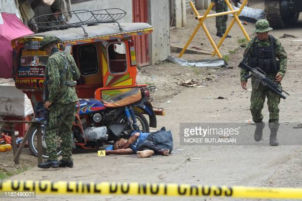Soldiers walk past the body of a man slumped beside a tricycle following an armed attack in front of the temporary headquarters of the army's First...