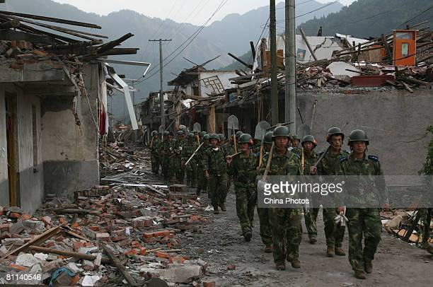 Soldiers walk through the ruins in the Hongbai Township on May 18 2008 in Shifang of Sichuan Province China A major earthquake measuring 79 on the...