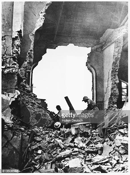 Soldiers walk through the ruins of a Government building after an air attack at Dakar in Senegal Africa during World War II