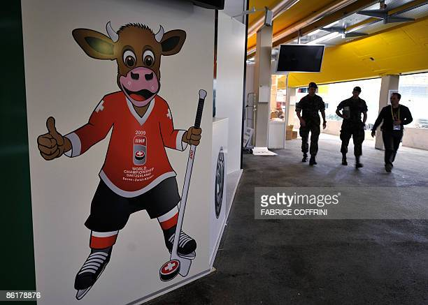 Soldiers walk towards a painting depicting a Swiss cow giving a thumbs up the logo of the 2009 IIHF Ice Hockey World Championships is pictured on...