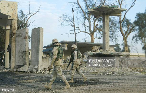 US soldiers walk towards the destroyed entrace of the Iraqi commando headquarters formally known as Qasr Dar alSalam a barracks for army personnel...