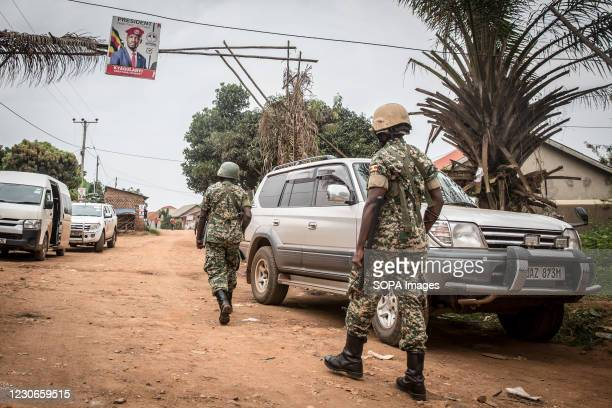 Soldiers walk towards the home of the opposition leader Bobi Wine whose real name is Robert Kyagulanyi, two days after Uganda's presidential...