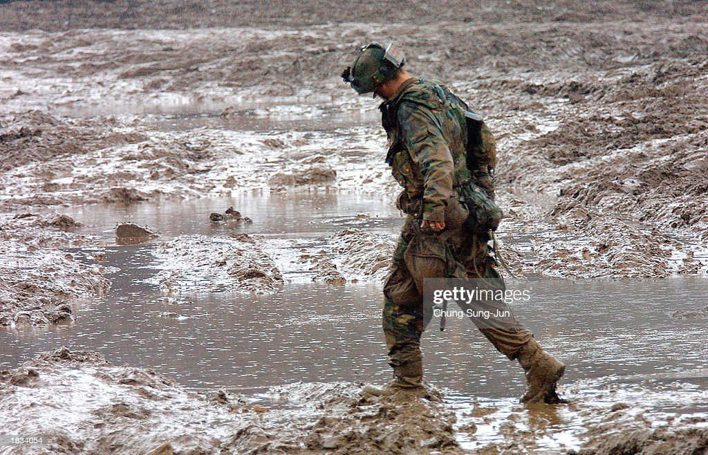 U S  soldiers walks through the mud during a military
