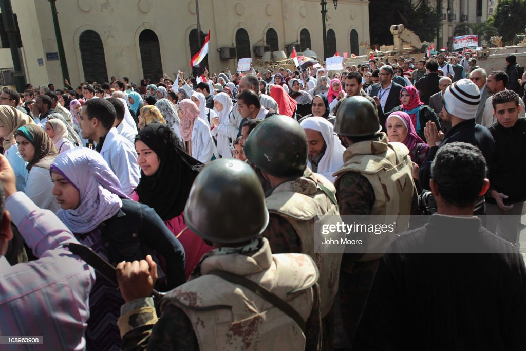 Soldiers watch as doctors, medical workers and students march through Cairo to join anti-government protests in Tahrir Square on February 10, 2011 in Cairo, Egypt. Thousands of workers from various unions across Egypt, including many medical workers, have gone on strike today with protestors calling for a nationwide general strike. The wave of strikes is increasing pressure on the government following more than two weeks of protests calling for the resignation of President Hosni Mubarak.