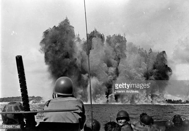 Soldiers watch as four tons of tetrytol placed by underwater demolition teams explode and open a hole in the reef allowing for an approach to the...