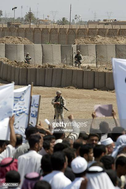 S soldiers watch as Iraqis demonstrate outside the Abu Ghraib prison May 5 2004 near Baghdad Some 2000 Iraqis demonstrated in front of the prison...