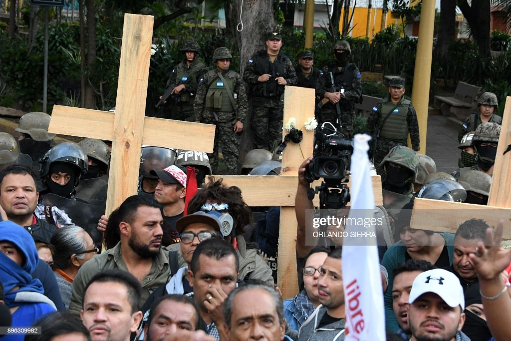 Soldiers watch supporters of the presidential candidate for the Opposition Alliance Against the Dictatorship, Salvador Nasralla, as they hold a demonstration outside the headquarters of the joint chiefs of staff of the armed forces, to protest the deaths that have occurred in clashes between demonstrators and the security forces since the disputed November 26 elections, in Tegucigalpa on December 20, 2017. Nasralla, who lost the controversial November 26 elections, said on his return to Honduras from the United States that he accepted the invitation from reelected President Juan Orlando Hernandez to engage in dialogue, but only to set a date for new elections after what he described as 'blatant electoral fraud.' /