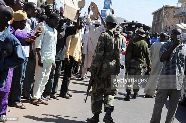 Soldiers watch youths protesting the killing of innocent lives in the central Nigerian city of Jos Plateau State on December 1 2008 The Nigeria...