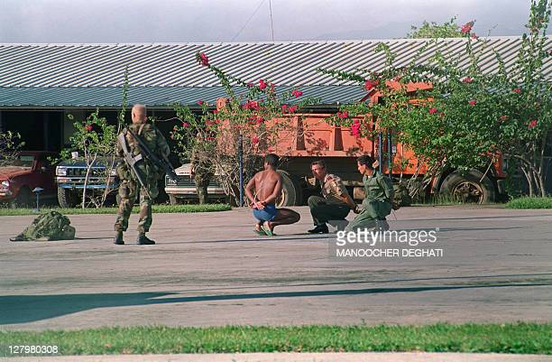 A US soldiers watches Panamanians captured during an operation against a military command post loyal to General Manuel Noriega on December 23 1989 in...