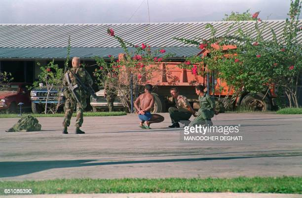 Soldiers watches Panamanians captured during an operation against a military command post loyal to General Manuel Noriega, on December 23, 1989 in...