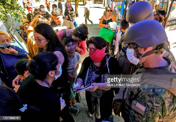 """Soldiers wear face masks as they stand guard outside a medical center in Concepcion, Chile, on March 19, 2020. - Chile declared a """"state of..."""