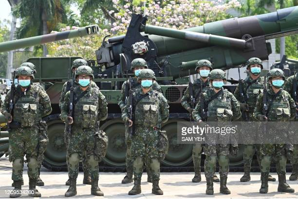 Soldiers wearing face masks amid the COVID-19 coronavirus pandemic stand in formation in front of a US-made M110A2 self-propelled howitzer during...