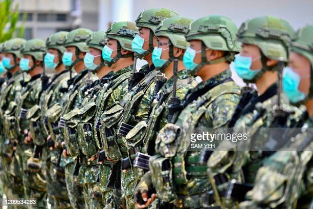 Soldiers wearing face masks amid the COVID-19 coronavirus pandemic listen to an address by Taiwan President Tsai Ing-wen during her visit to a...