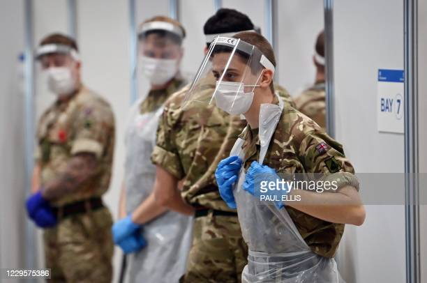 Soldiers wearing full PPE in the form of face shields, gloves, face masks and bibs wait to assist covid testing at a coronavirus rapid testing centre...