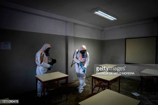 TOPSHOT Soldiers wearing protective gear conduct a disinfection operation at a high school in Amadora in the outskirts of Lisbon on April 29 2020...