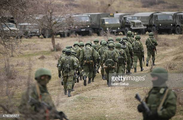 Soldiers who were among several hundred that took up positions around a Ukrainian military base walk towards their parked vehicles in Crimea on March...