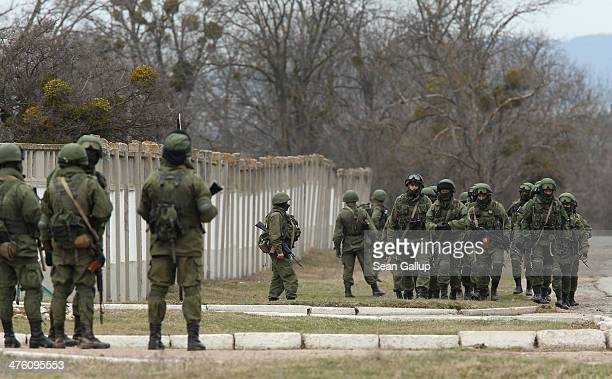 Soldiers who were among several hundred that took up positions around a Ukrainian military base walk on the base's periphery in Crimea on March 2...