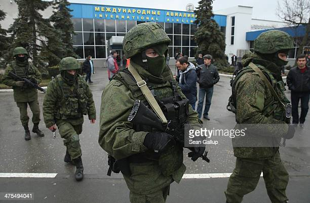 Soldiers, who were wearing no identifying insignia and declined to say whether they were Russian or Ukrainian, patrol outside the Simferopol...