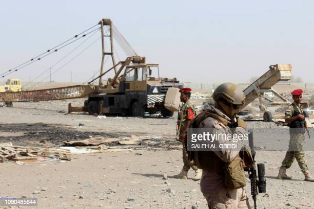 Soldiers with a military coalition in Yemen backed by Saudi Arabia and the United Arab Emirates stand guard outside a damaged warehouse of Yemen's...
