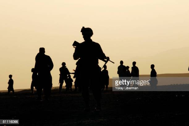 Soldiers with an artillery supply infantry unit patrol April 24, 2004 in Morgan Keckeh, Afghanistan. In this area there are many locals still...