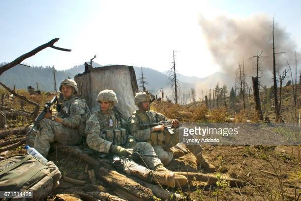 Soldiers with Battle Company 173rd Division stand guard behind a tree stump as they wait for a medevac to come and take away the body of one of their...