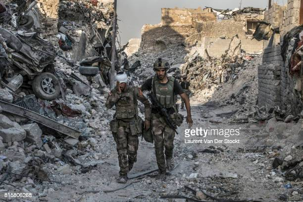 Soldiers with Iraqi special forces walk through a debrisstrewn alley after they regained control over the last districts of Mosul's Old City