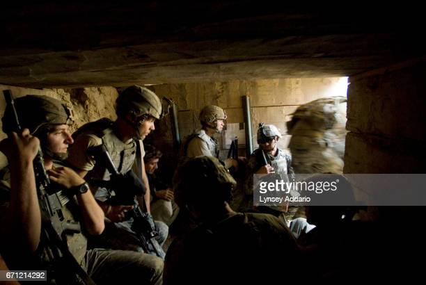 Soldiers with the 173rd division and Afghan workers on the base moments before a mortar fired by the Taliban lands about 20 feet from the opening of...