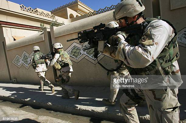 Soldiers with the 1st Battalion 5th Infantry Stryker Brigade Combat Team of the 25th Infantry Division out of Ft Lewis Washington rush down a street...