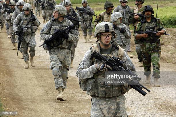 US soldiers with the 1st Battallion 6th Regiment 2nd BCT 1st Armoured Division patrol an area with Iraqi soldiers in Owesat southwest of Baghdad in...