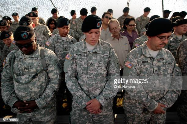 Soldiers with the 1st Infantry Division bow their heads in prayer before a deployment ceremony for another tour in Iraq August 13 2009 at Fort Riley...