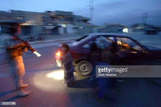 S soldiers with the 25th Infantry Division approach a car immediately after they fired on the vehicle January 18 2005 in Tal Afar Iraq The troops...