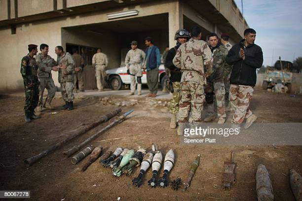 Soldiers with the 2nd Brigade of the 5th Iraqi Division of the Iraqi Army stand beside a weapons cache found while clearing an area of insurgents...