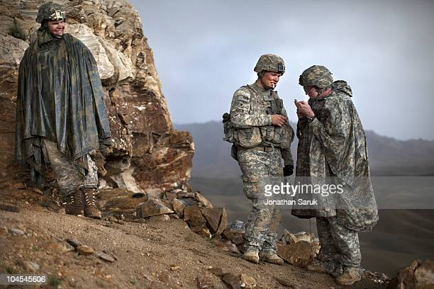 US soldiers with the 3rd Brigade 10th Mountain Division take a cigarette break in the rain while constructing an observation post at a new combat...