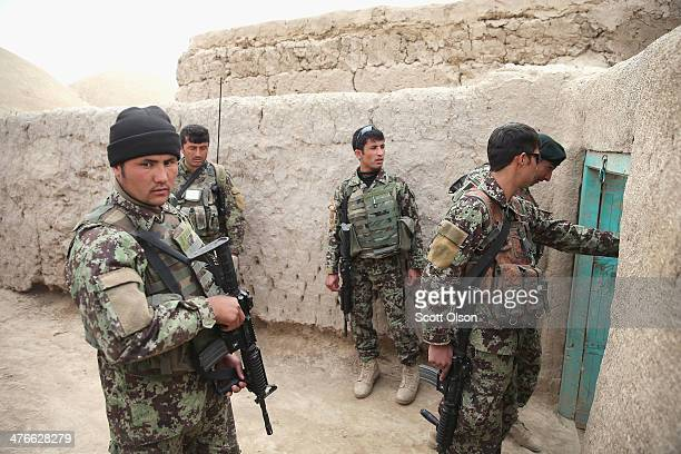 Soldiers with the Afghan National Army patrol through a village with soldiers from the US Army's 4th squadron 2d Cavalry Regimentsit on March 4 2014...