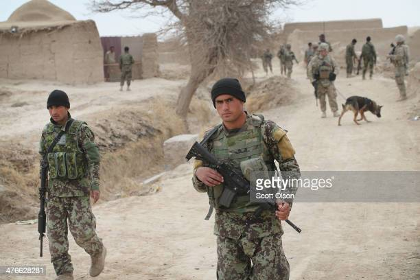 Soldiers with the Afghan National Army patrol through a village with soldiers from the U.S. Army's 4th squadron 2d Cavalry Regimentsit on March 4,...