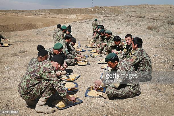 Soldiers with the Afghan National Army's National Engineer Brigade take a break for lunch as they train with US Navy Seabees from Naval Mobile...