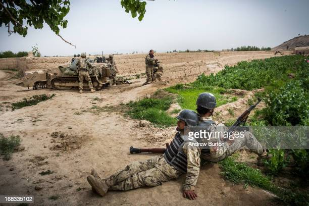Soldiers with the Afghan National Civil Order Police lean against each other to rest during a twoday joint mission with the United States Army's 3rd...