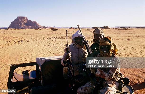 Soldiers with the Forces Armees Nationales Chadiennes or National Army of Chad stand guard with assault rifles along the road on route to Wadi Doum...