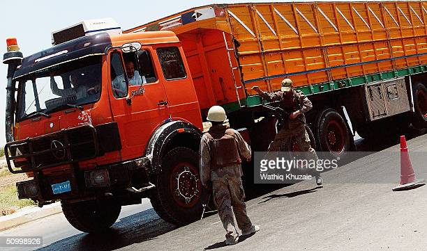 Soldiers with the Iraqi Civil Defence Corp search a truck at a checkpoint on the way to the Iraqi city of Baqouba on June 26 2004 near Baqouba Iraq...
