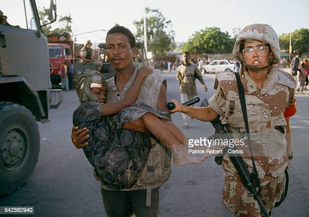 Soldiers with the United States Marines carry a young wounded Somali boy in the street after 28000 Marines were sent during Operation Restore Hope to...
