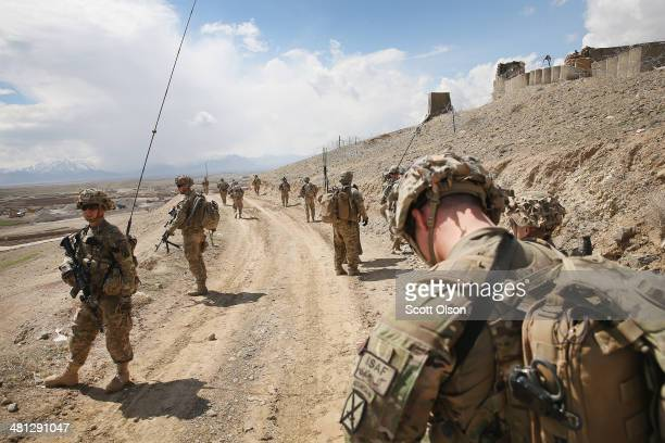 Soldiers with the US Army's 2nd Battalion 87th Infantry Regiment 3rd Brigade Combat Team 10th Mountain Division patrol on the edge of a village...