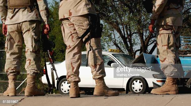 US soldiers with their Iraqi translator secure the scene of a car bomb explosion September 21 2004 in Baghdad Iraq A car bomb exploded near a US...