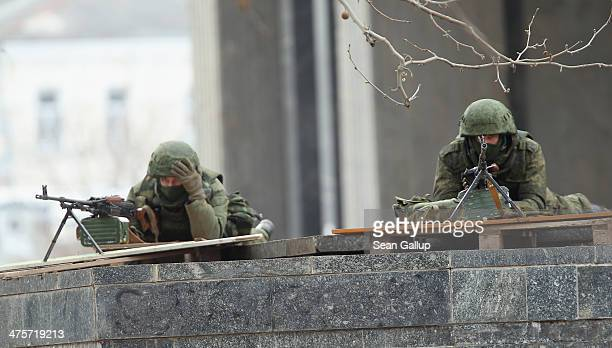Soldiers without identifying insignia man machine guns outside the Crimean parliament building shortly after several dozen soldiers took up positions...