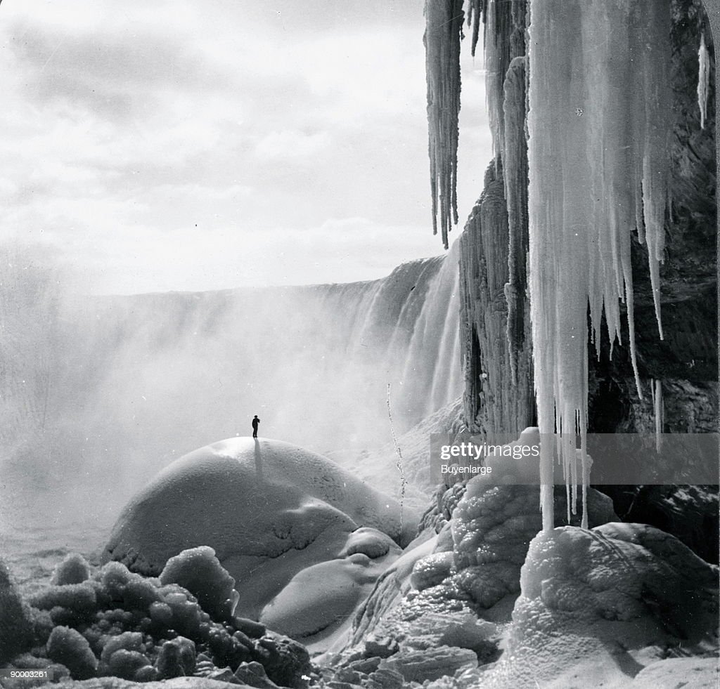 Sole Adventurer stand on an ice dome beneath the icicled Niagara Falls in a Frozen Wonderland