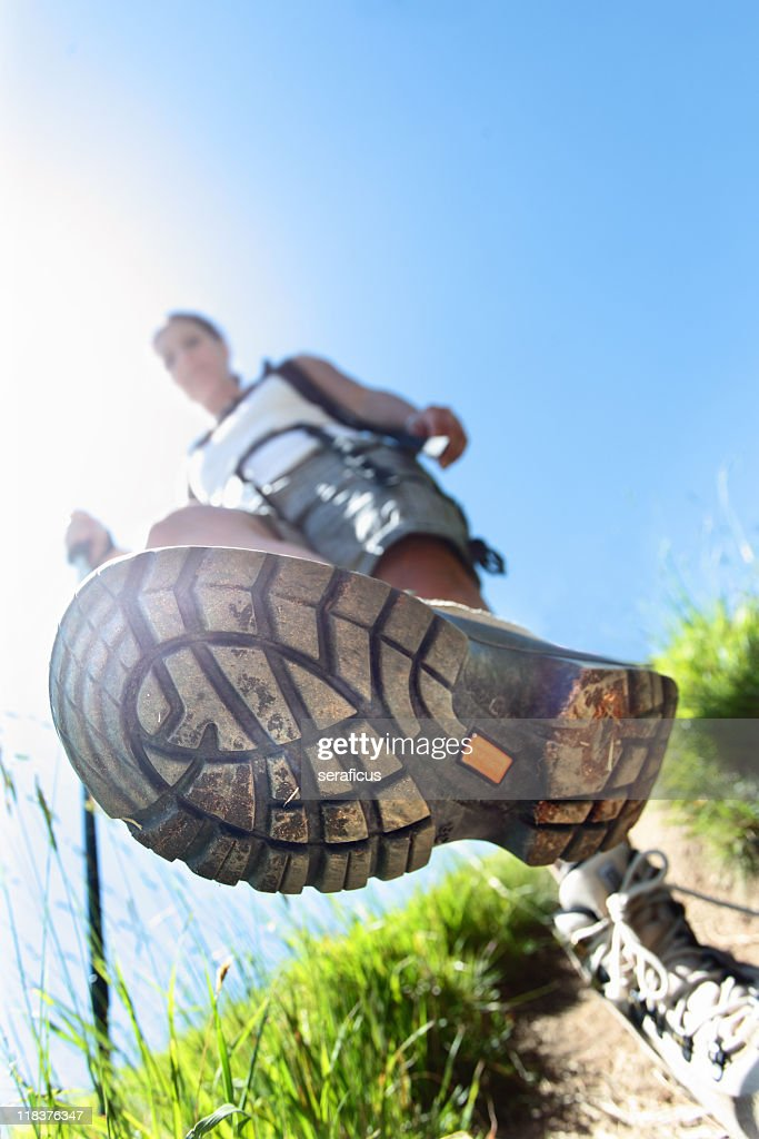 Sole of hikers sneaker as he is walking down the trail : Stock Photo