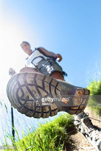 Sole of hikers sneaker as he is walking down the trail