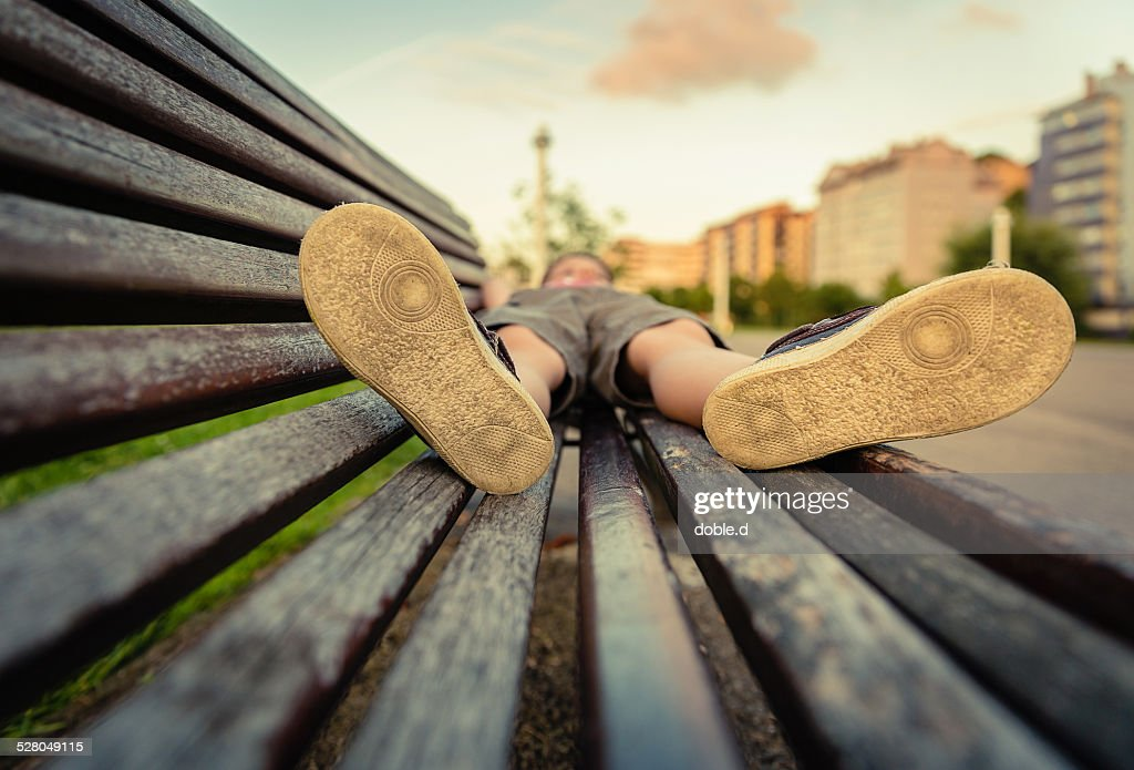 Sole shoes closeup of boy lying on a wooden bench : Stock Photo