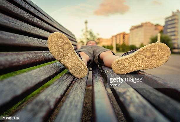sole shoes closeup of boy lying on a wooden bench - 靴底 ストックフォトと画像